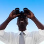 Businessman looking through binoculars — Stock Photo