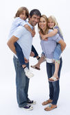 Family giving children piggyback ride against white — Stock Photo