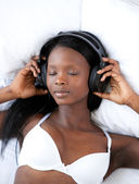 Radiant woman listening music lying on her bed — Stock Photo