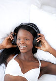 Radiant woman listening music lying on her bed — Stok fotoğraf