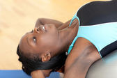 Afro-american woman doing sit-ups with a gym ball — Stock Photo