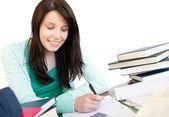 Niña adolescente sonriente estudiando en un escritorio — Foto de Stock