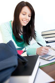 Cheerful teen girl studying on a desk — Stock Photo