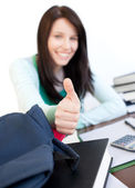 Attractive teen girl with thumb up studying — Stock Photo