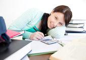 Lächelnd schüler ihre hausaufgaben auf dem schreibtisch — Stockfoto