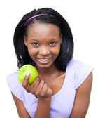 Smiling young woman eating an apple — Stock Photo