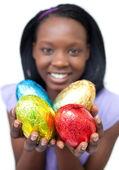 Mujer étnica feliz mostrando los huevos de Pascua — Foto de Stock