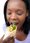 Afro-american woman eating a wrap — Stock Photo