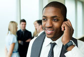 Afro-American businessman on phone in office — Stock Photo