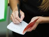Blonde zakenvrouw schrijven op een notitieblok — Stockfoto