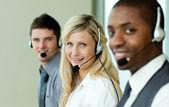 Tres negocios trabajando con auriculares — Foto de Stock