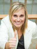 Businesswoman smiling with her thumb up — Stock Photo