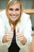 Businesswoman smiling at the camera with her thumbs up — Stock Photo