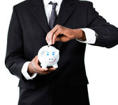 Close-up of a Businessman putting money in his piggy bank — Stock Photo