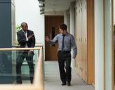 Affärsmän säger adjö i en korridor — Stockfoto