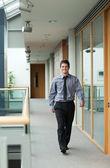 Handsome businessman walking through a corridor — Stock Photo