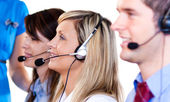 Team of talking with headsets on — Stock Photo