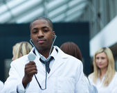 Handsome Afro-American doctor leading his team — Stock Photo