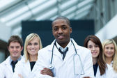Afro-American doctor leading his team with folded arms — Stock Photo