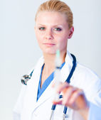 Serious Doctor holding a needle with hint of a smile — Stock Photo