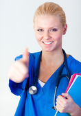 Doctor with her thumb up with focus on face — Stock Photo
