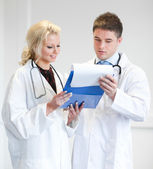 Two nice doctors looking at a report — Stock Photo