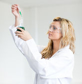 Woman in lapcoat looking at chemicals — Stock Photo