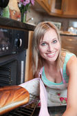Radiant woman baking bread — Stock Photo