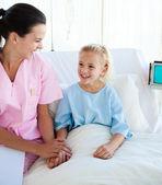 Usmíval se holčičky sedící na nemocniční posteli s jejím lékařem — Stock fotografie