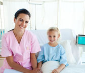 Female doctor with her little patient sitting on a hospital bed — Foto de Stock