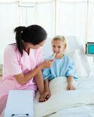 Young nurse attending a child patient — Stock Photo