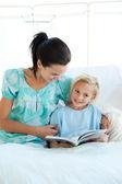 Flicka på en sjukhussäng läsning med sin mor — Stockfoto