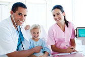 A doctor checking the pulse on a smiling little girl — Stock Photo
