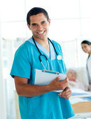 Attractive male doctor holding a medical clipboard — Stock Photo