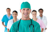 Smiling surgeon in front of his team — Stock Photo