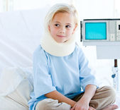 Little girl with a neck brace sitting on a hospital bed — Stock Photo