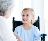 Blond little girl sitting on a wheelchair talking with her grand — Stock Photo
