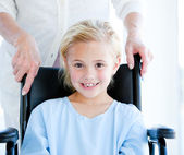 Adorable little girl sitting on a wheelchair — Stock Photo
