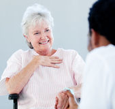 Senior woman sitting on a wheelchair talking with her doctor — Stock Photo