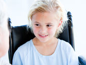 Blond little girl sitting on a wheelchair — Stock Photo