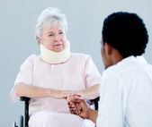 Senior woman sitting on a wheelchair with a neck brace talking w — Stock Photo