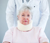 Portrait of a senior woman with a neck brace sitting on a wheelc — Stock Photo