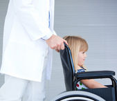 Smiling little girl sitting on the wheelchair supported by a doc — Stock Photo