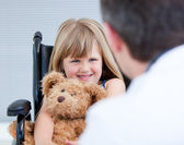 Smiling little girl sitting on the wheelchair with her teddy bea — Stock Photo