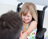 Reserved little girl sitting on the wheelchair — Stock Photo