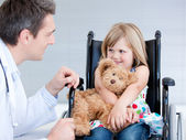 Smiling little girl sitting on the wheelchair lokking at the doc — Stock Photo