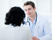 Handsome doctor talking with his patient for the annual check-up — Stock Photo
