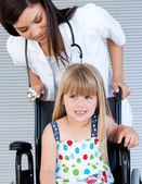 Smiling cute girl sitting on the wheelchair — Stock Photo