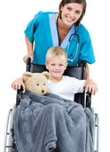 Beautiful female doctor carrying adorable little boy in the whee — Stock Photo