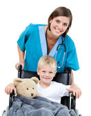 Nice female doctor carrying adorable little boy in the wheelchai — Stock Photo